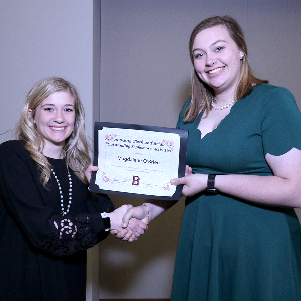 Girl presents certificate award to a woman