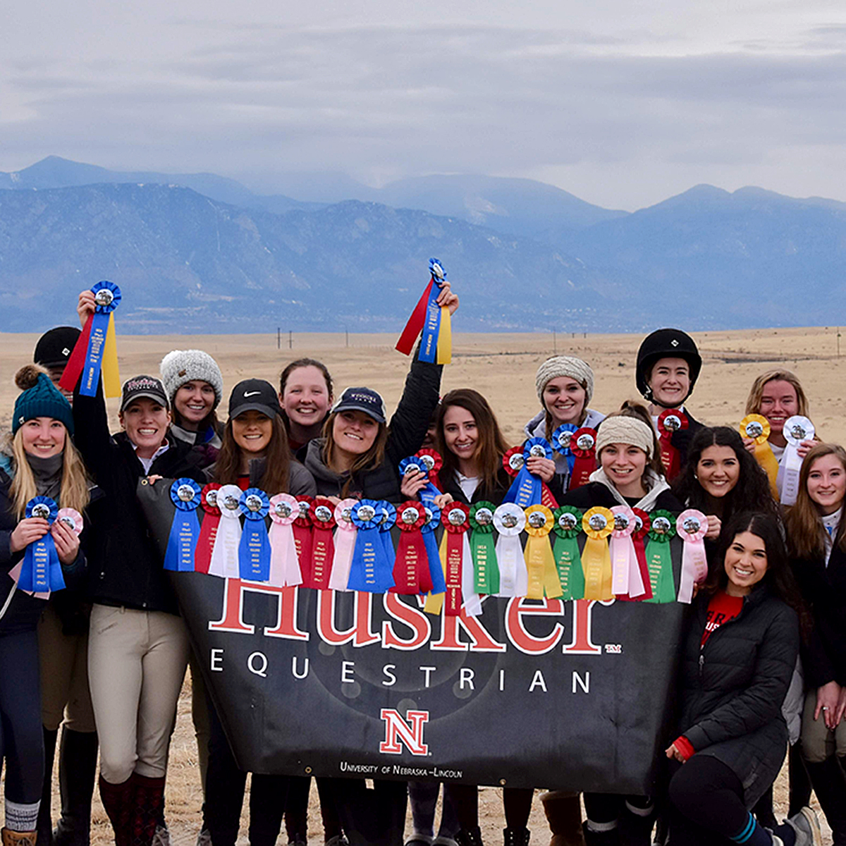 Members of the 2018 Equestrian Team pose for a                         picture in front of a landscape of mountains.