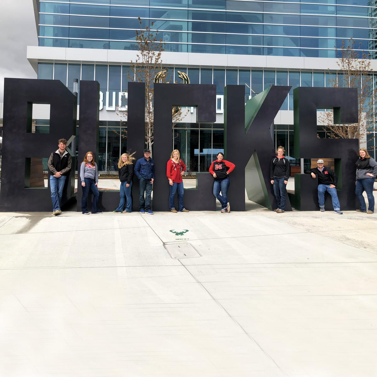 Student posing for a picture infront of big letter-sculpture spelled B U C K S.