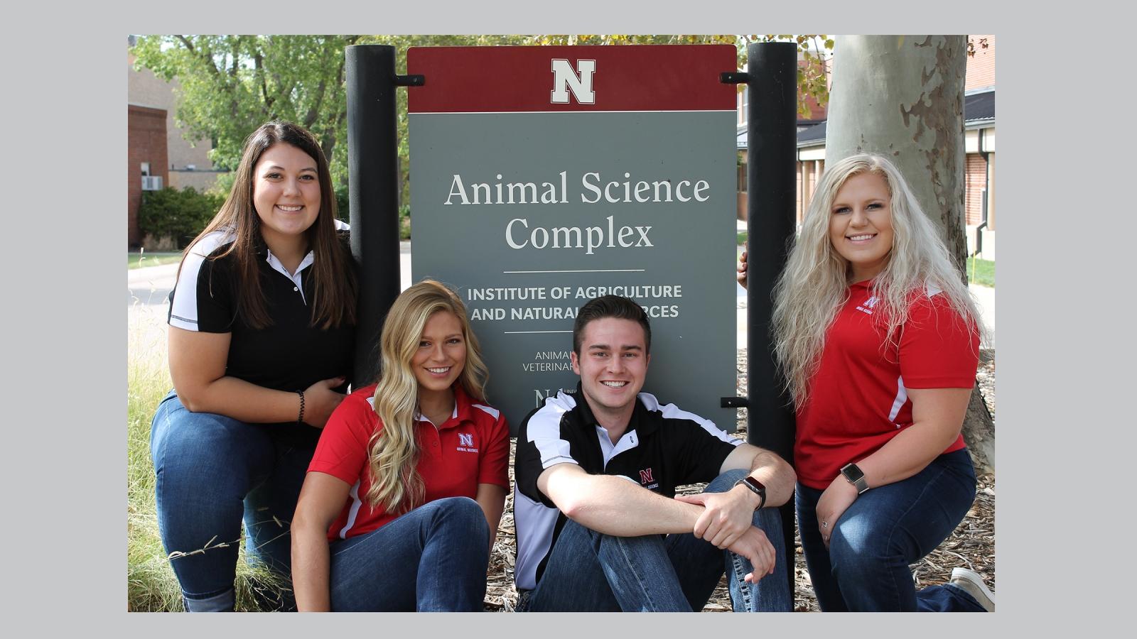 Four Animal Science Ambassadors pose around the animal science sign.