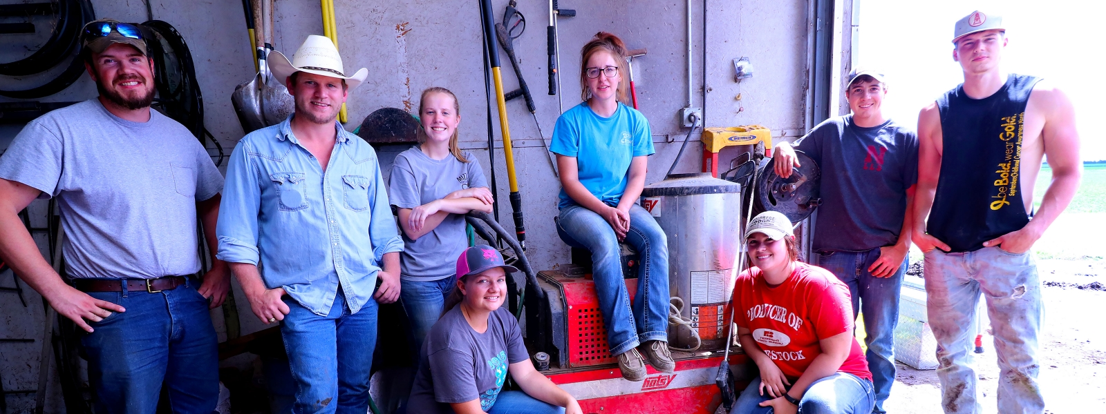 A group of interns pose for a picture in a tool shed.