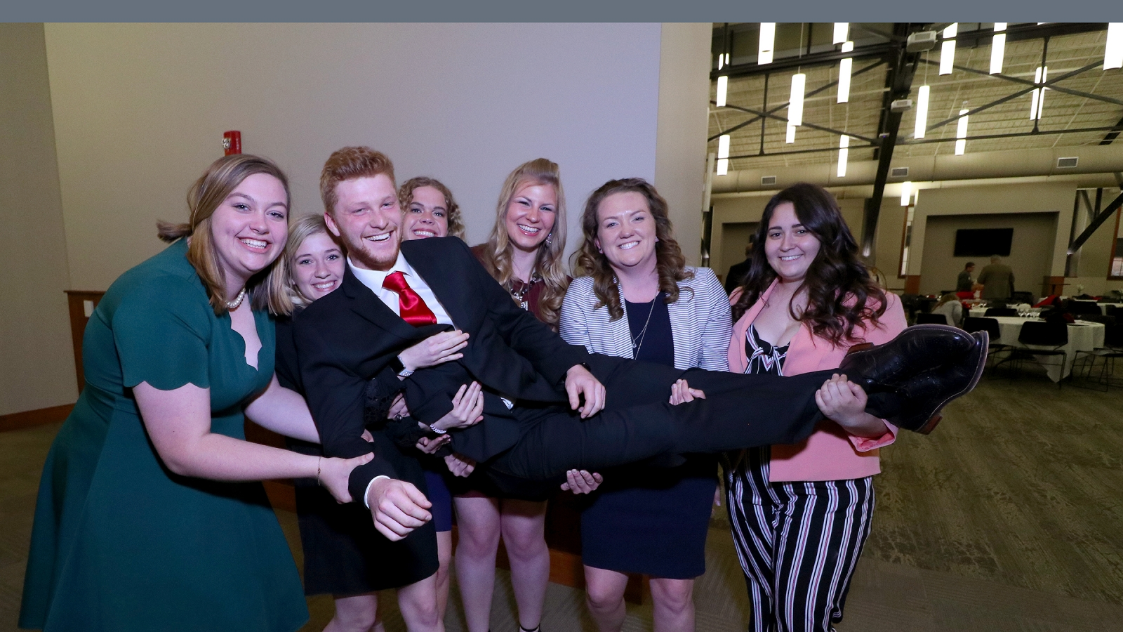 a group of girls lifts a man who lays down in their arms while posing for the camera