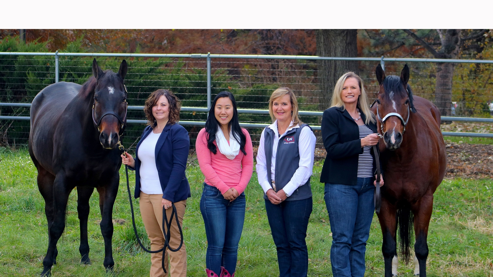 four women stand in between two horses