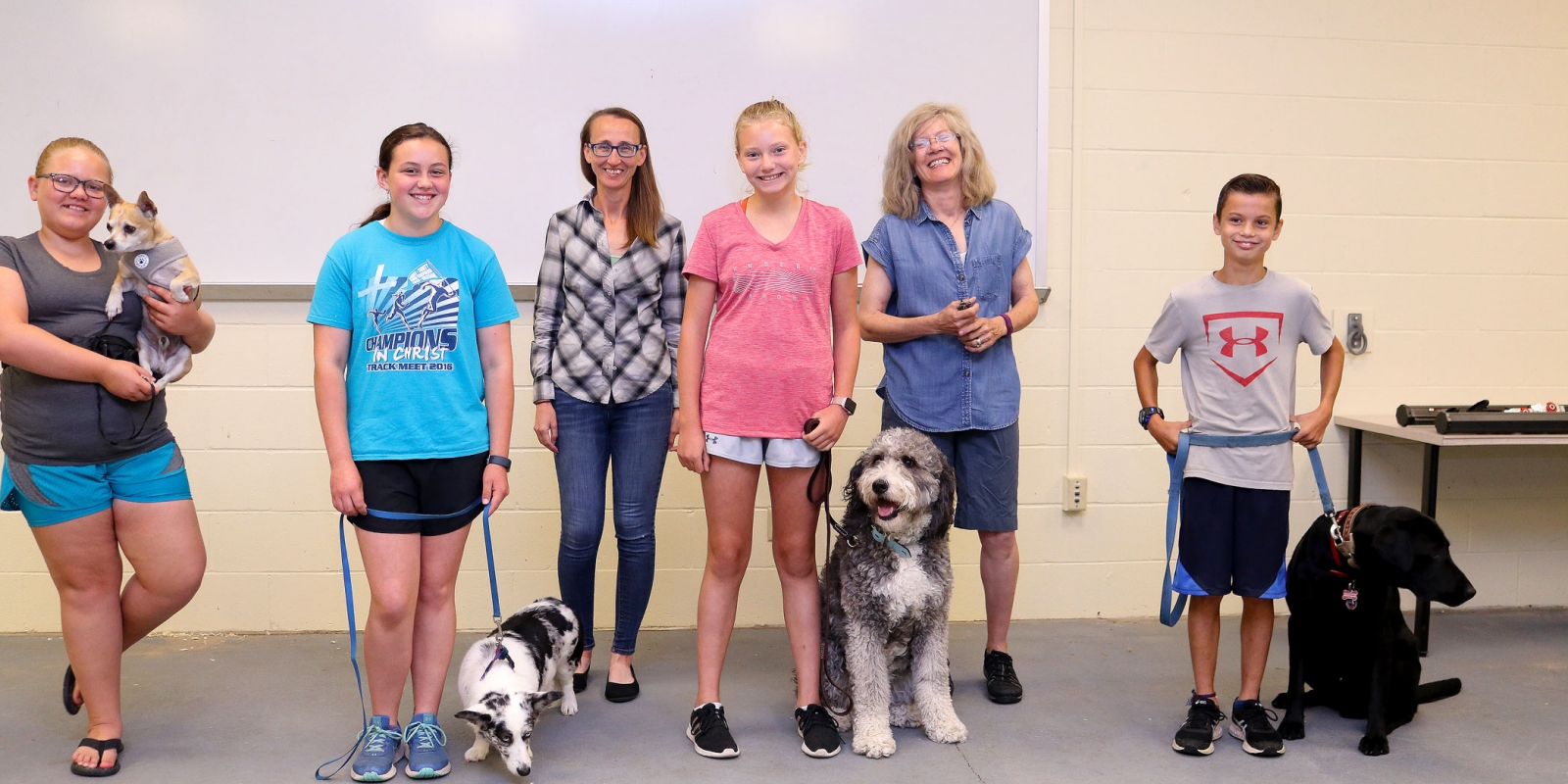 Group o 4-H kids and two dog trainers pose for a photo