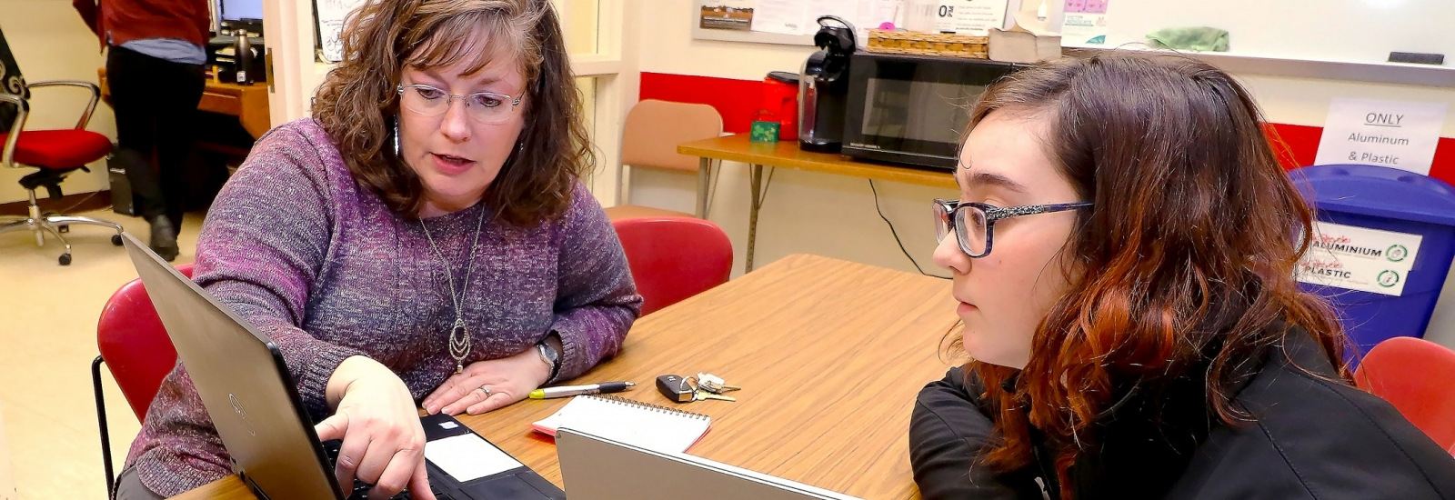 An academic advisor seated at a table with a female student both looking at a laptop screen while the academic advisor points at the screen