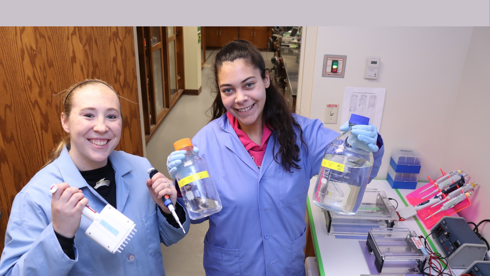 two Girls in the lab doing experiment hold up bottles with fluid in it.